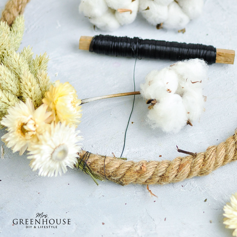 Trockenblumen mit Draht an Kranz binden