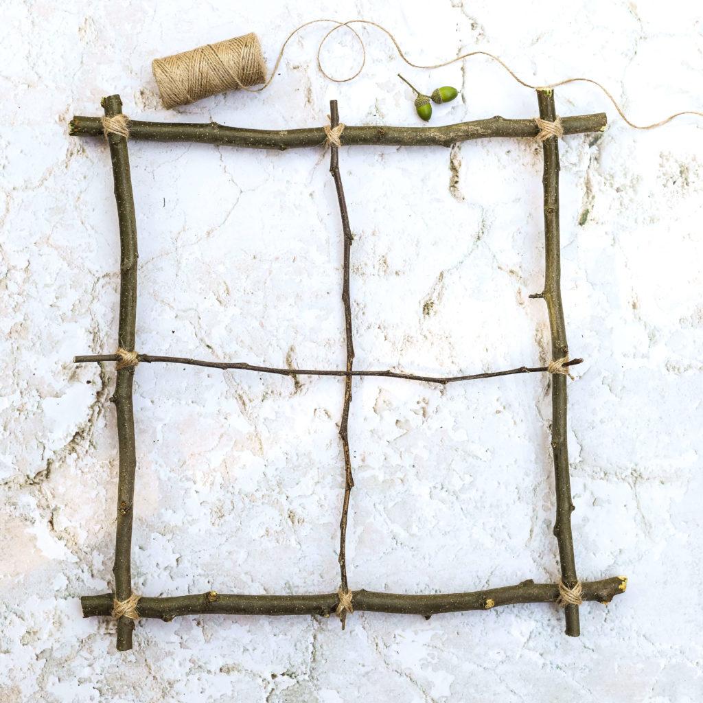 Fensterkreuz aus dünnen Ästen befestigen