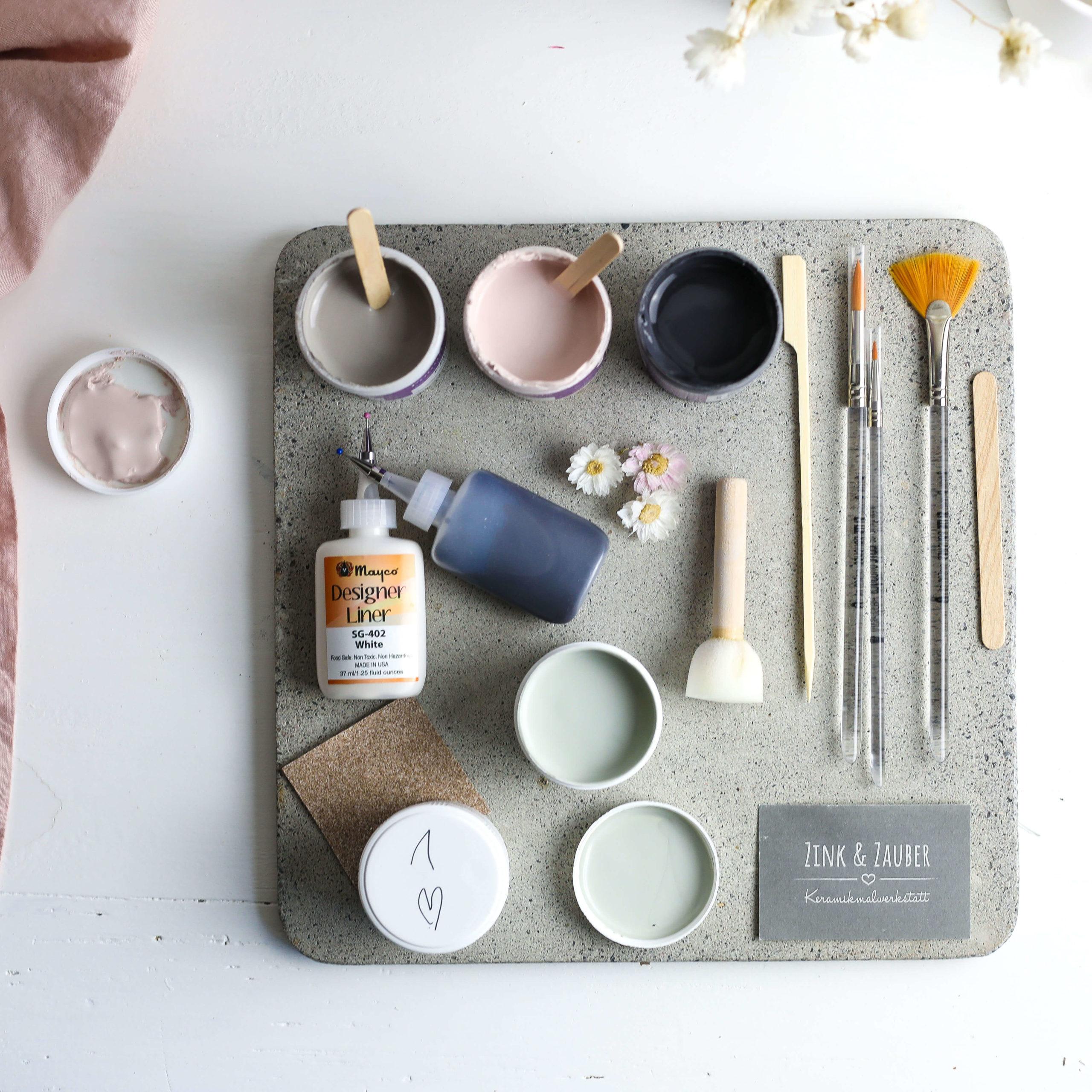 Farben und Pinsel zum Bemalen von Keramik