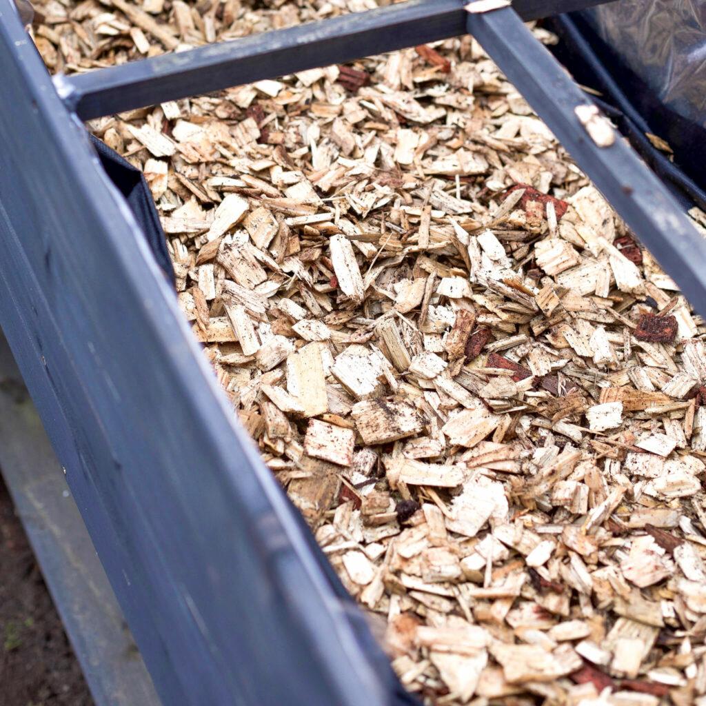 Holzschnitzel in Tischbeet füllen