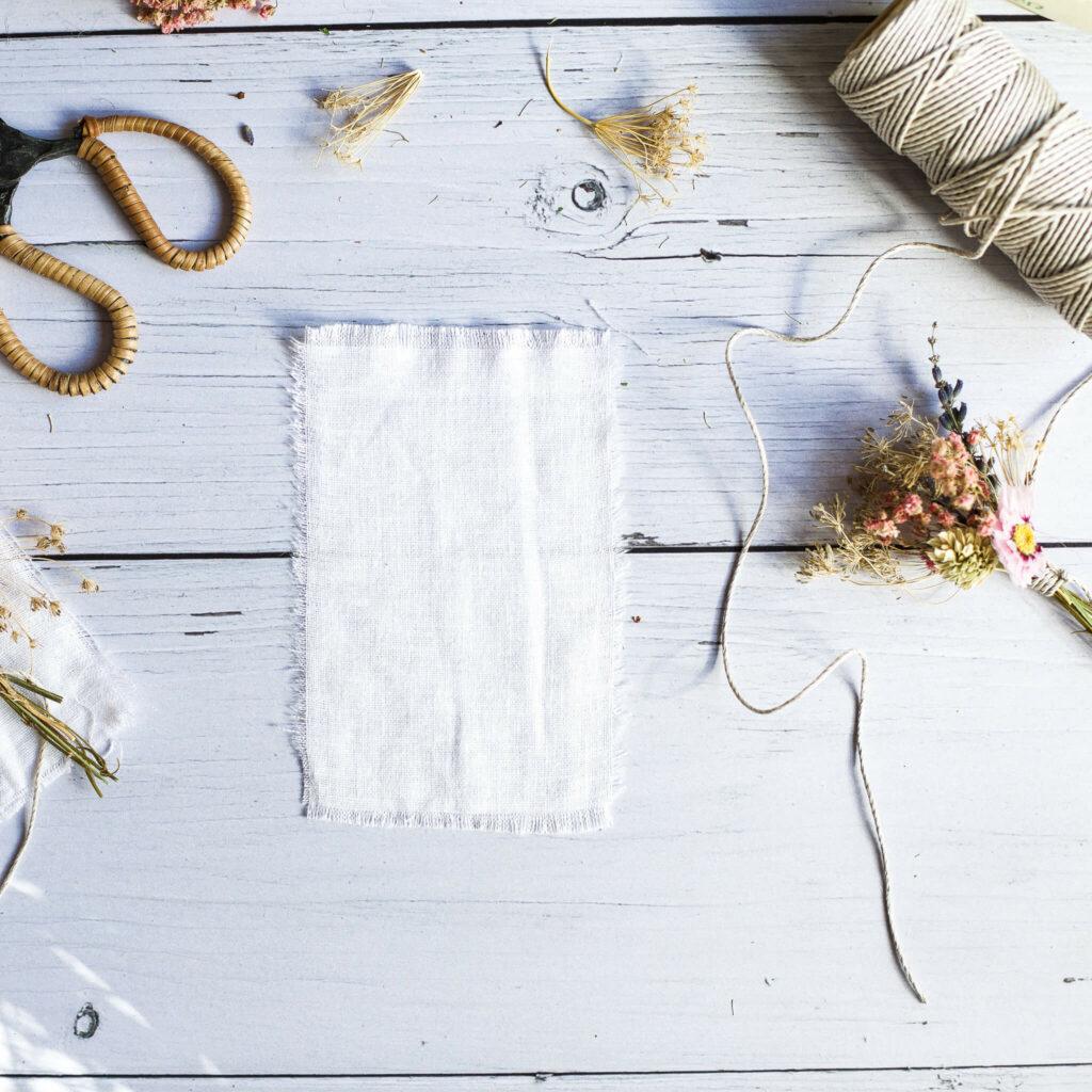 Stoff für Karte mit Trockenblumen zurecht schneiden