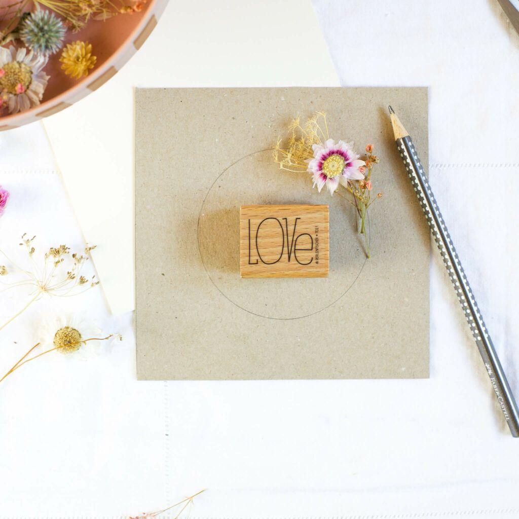 Trockenblumenkranz auf Papier aufkleben